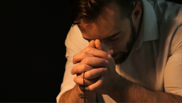 A man with rosary praying